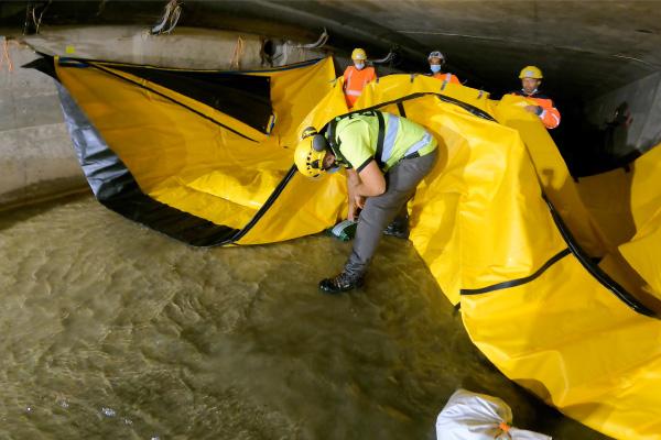 Legen Sie Kiesbeutel unter den flexiblen Damm Water-Gate © auf den Boden, um die Reibungskräfte zu erhöhen.